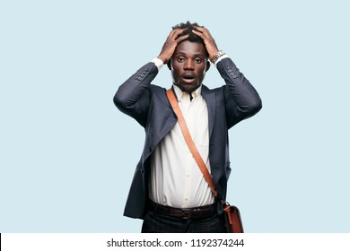 young black businessman shouting with a crazy, amazed look of surprise, holding head with both hands.