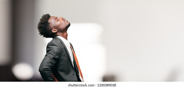 young black businessman smiling and looking up and sideways, towards the sky or to the spot where the publicist may place a concept or message.