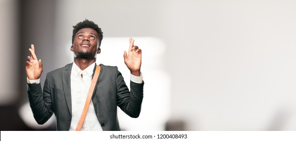 young black businessman smiling mischeviously while swearing a promise, cheating, crossing fingers while making an oath.