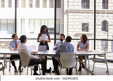 Young black businesswoman addressing colleagues at a meeting