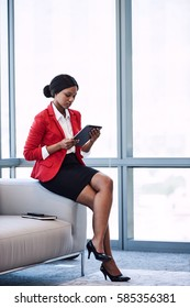 Young black businesswoman sitting on the edge of a sofa in a business lounge while looking at the screen of the digital tablet that she is holding in her hands.