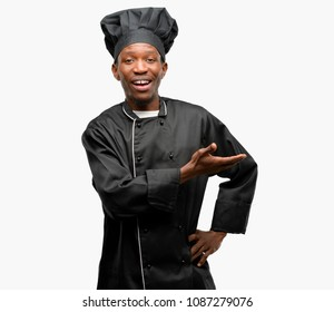 Young black cook wearing chef hat holding something in empty hand