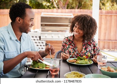 Young black couple eating lunch at a table in the garden