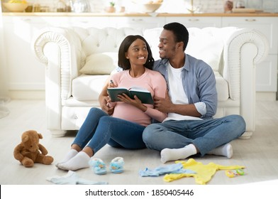 Young black couple expecting baby and writing checklist of child stuff for maternity hospital, sitting on floor in living room. Positive future parents making list for birthing center at home