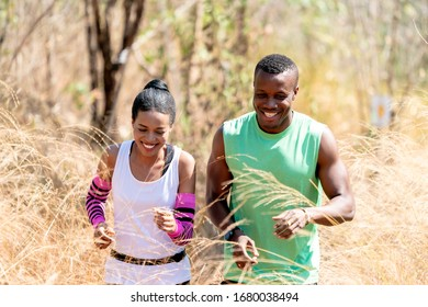 Young Black Couple Running at Forest Trail. Sportive man and woman Training Outdoors.American Couple Running Outside in Forest