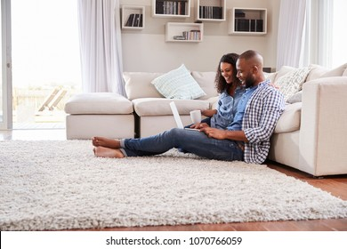 Young black couple sit on the floor using laptop, side view