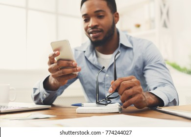Young black employee at workplace using mobile phone, checking social media on smartphone, taking break, copy space
