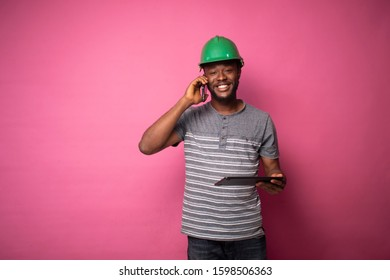 young black engineer making a phone call while viewing his tablet