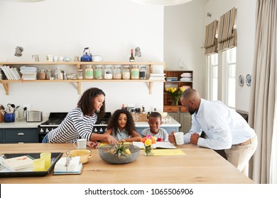 Young black family busy together in their kitchen
