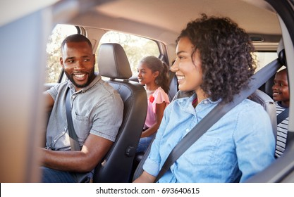 Young black family in a car on a road trip smiling