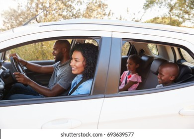 Young black family in a car smile on the road trip
