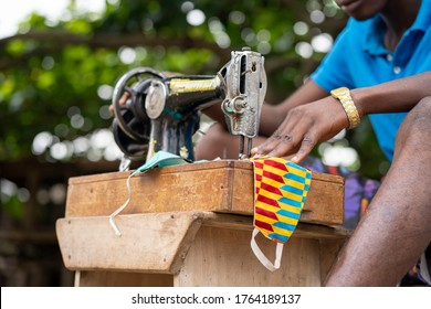 young black fashion designer sewing nose mask at home during covid-19  lockdown-close up shot of sewing machine and nose mask-locally made nose mask sewn by african man
