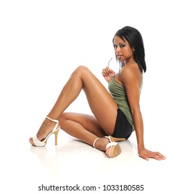 Young black fashion model wearing shorts and high heels isolated on a white background