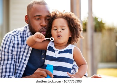 Young black father and daughter blowing bubbles outside