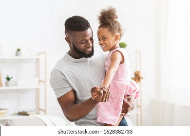 Young black father holding little daughter dressed in beautiful dress, dancing together at home