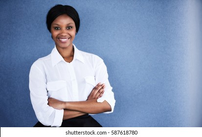 Young black female business executive smiling at camera with her arms crossed while smiling at the camera and standing against a textured blue background.