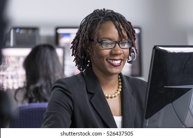 Young black female professional working at a computer in an office, smiling