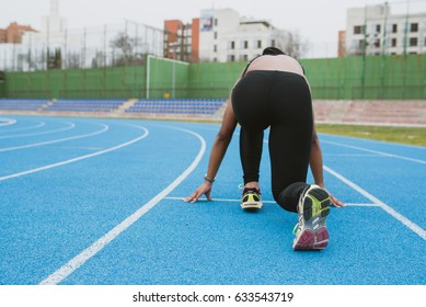 Young black female in sportswear sitting in pose ready to start running on sport ground.
