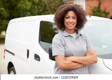 Young black female tradesperson standing next to her white van with arms crossed, close up