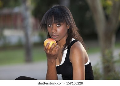 Young black girl with apple in the park.