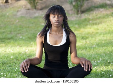 Young black girl doing yoga in the park