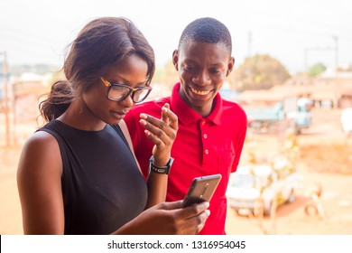 young black girl and guy looking at something interesting on a mobile phone together
