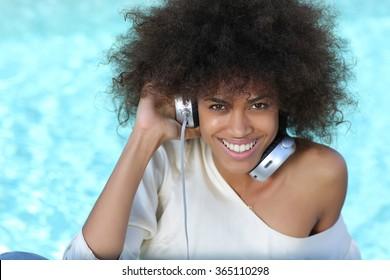young black girl listening music at big headphones near pool during spring break.
