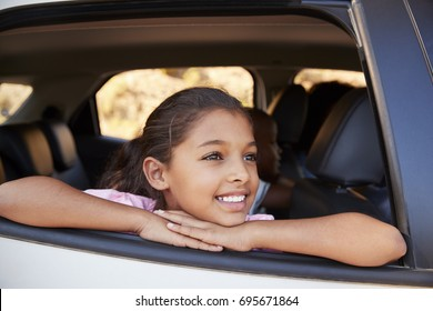 Young black girl looking out of car window smiling, front view