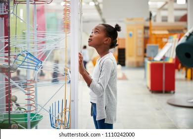 Young black girl looking at a science exhibit, close up