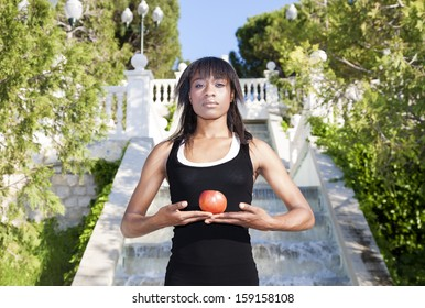 Young black girl relaxing in the park with apple