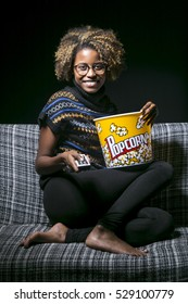 Young black girl sitting on the sofa watching TV with popcorn