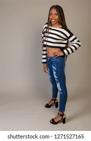 Young Black Girl in striped shirt with exposed midriff posing in studio