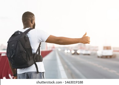 Young Black Guy Is Hitchhiking On The Bridge Road, carrying backpack, rear view