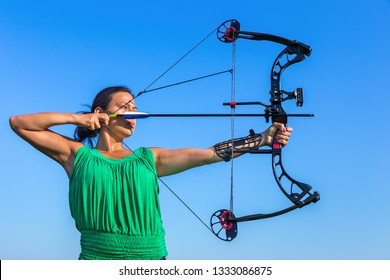 Young black haired colombian woman aiming arrow of compound bow in blue sky
