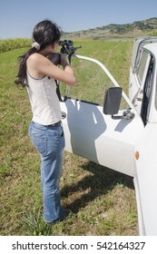 Young black haired girl shooting with sniper rifle next to a white car