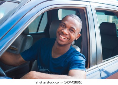 young black handsome cab driver smiling inside his blue car