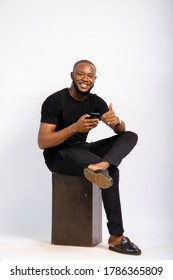 young black handsome man sitting, using his smartphone with happiness