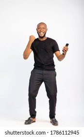young black handsome man standing jubilating over something he saw on his smartphone