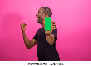 young black happy man holding out his smartphone and jubilating