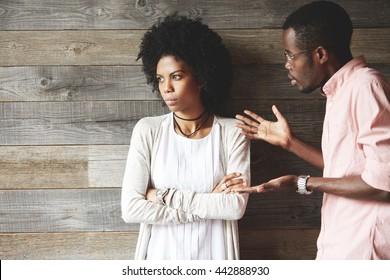 Young black indignant male gesticulating, arguing with his dark skinned girlfriend, who is standing against wooden wall with crossed arms, looking away with deeply offended expression on her face