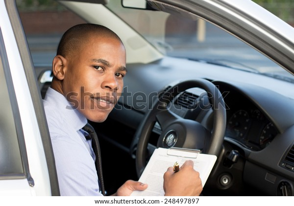 Young Black inspector, business man inspecting car, doing a checklist