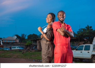 young black male and female engineers smiling and giving a thumbs up while standing back to back at a mechanic site workshop