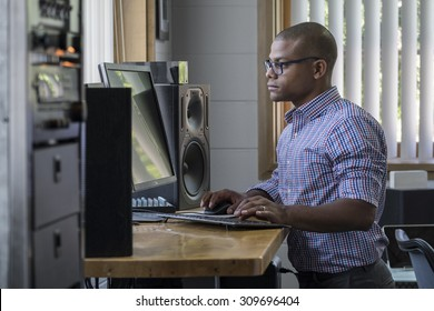Young black male standing at his computer desk in an office