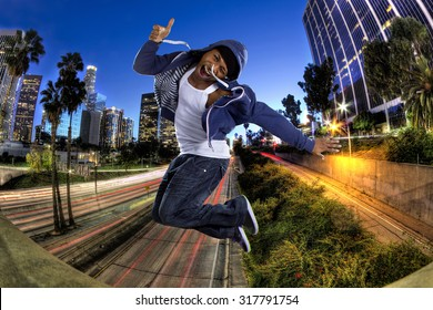 Young black male wearing a blue hoodie jumping in Los Angeles.  The background is the downtown LA freeway.