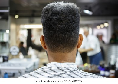 Young black man in barbershop,back view.Unshaven nape and neck of african male model in barber shop salon.Male beauty treatment process