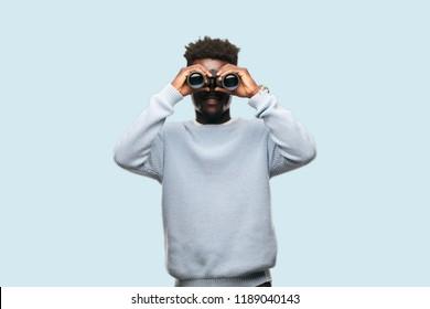 young black man with binoculars looking far
