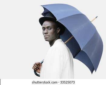 Young black man with a blue umbrella wearing a bowler hat.