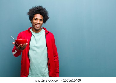 young black man with a breakfast bowl against blue grunge wall