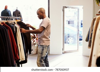 Young black man browsing through clothes on a rail in a shop