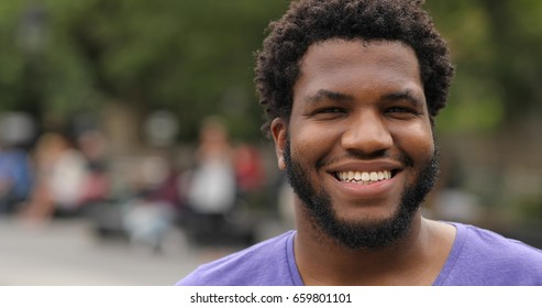 Young black man in city park face portrait smile happy